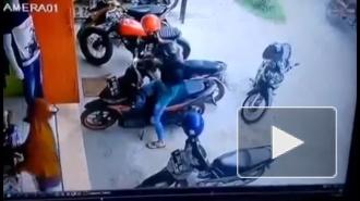 Девушка выезжает с парковки на скутере.
